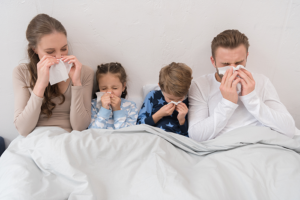 four member family in bed blowing noses