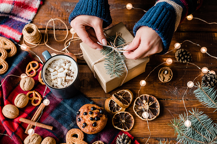 Hands of girl making bow on top of wrapped giftbox surrounded by sweet food, walnuts, garlands and hot cappuccino in mug